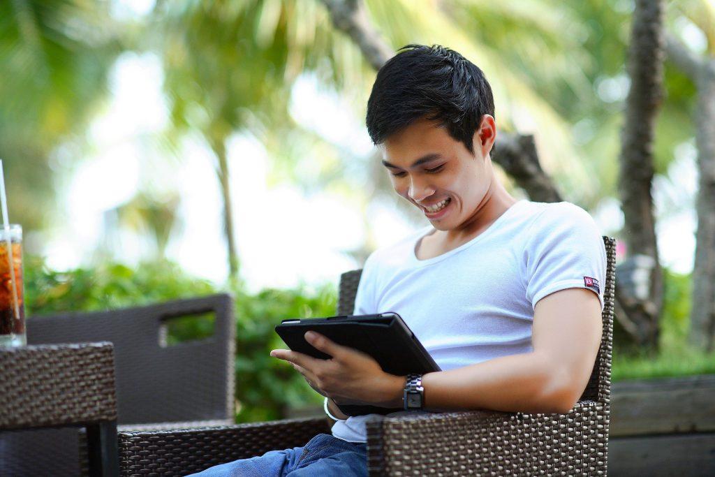 Homme content qui signe électronique un contrat sur sa tablette